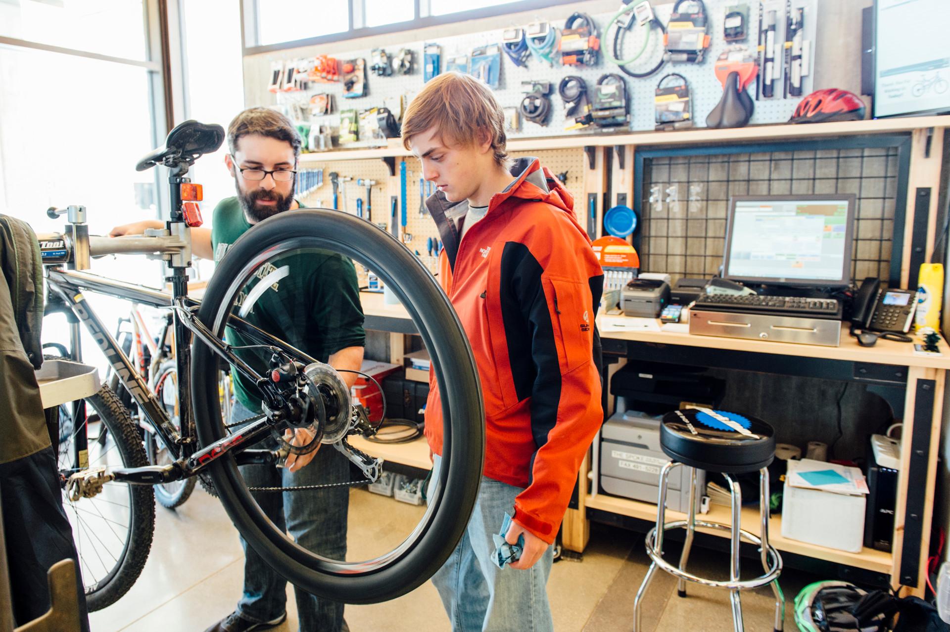 people examining a bike in the laurel village bike repair shop