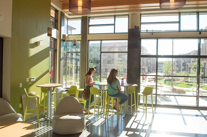 students at table in aggie village common area