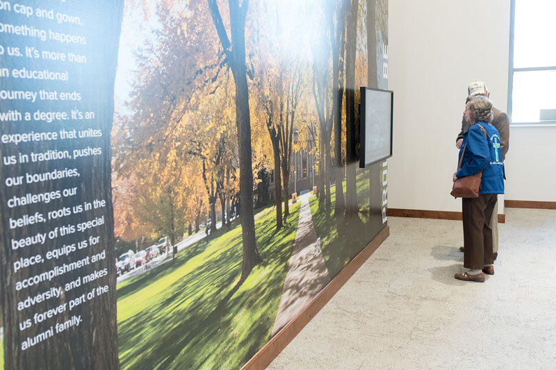 Couple looking at interactive display in the Iris and Michael Smith Alumni Center